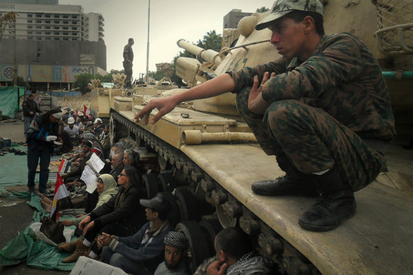 Tahrir Square protesters sitting in front of the tanks.