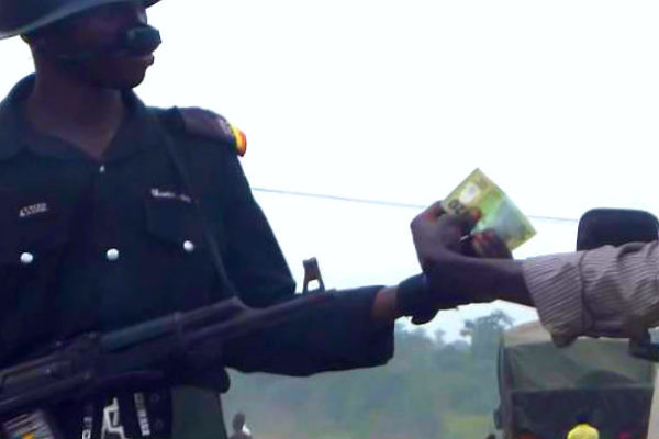 A Nigerian police officer collecting N20 from a driver