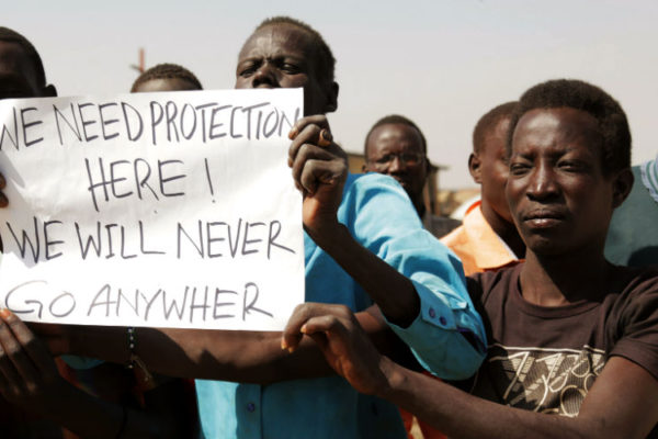"South Sudanese holding a sign reading ""We Need Protection"""