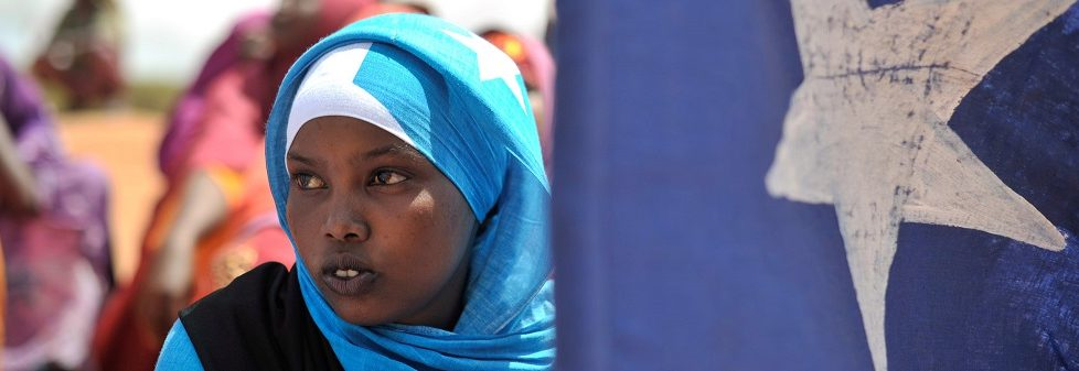 A young woman holds the Somali flag. PHOTO / Tobin Jone