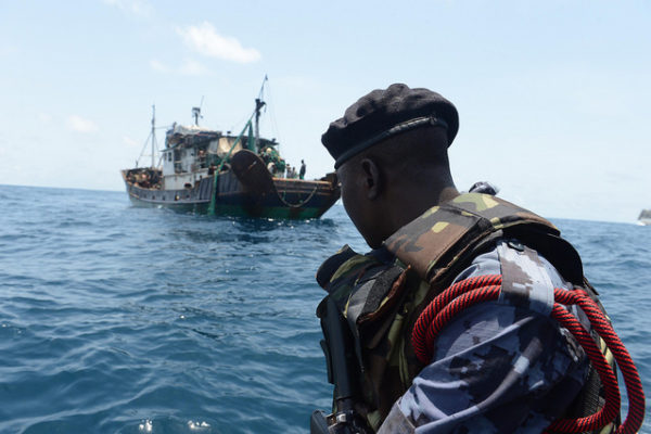 A member of the Ghanaian maritime police looks at a suspected illicit fishing vessel prior to boarding. [Photo: U.S. Naval Forces Europe-Africa]
