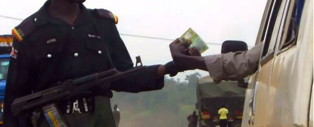 A Nigerian police officer collects N20 from a driver