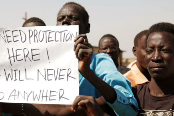 "Several South Sudanese hold a sign reading, ""We Need Protection Here, We Will Never Go Anywhere"""