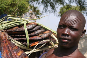A Mundari fisherman carrying smoked fish in Terekeka, Central Equatoria State.