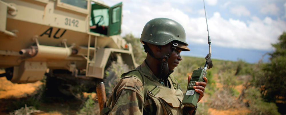 An AMISOM field commander in front of an armoured personnel carrier