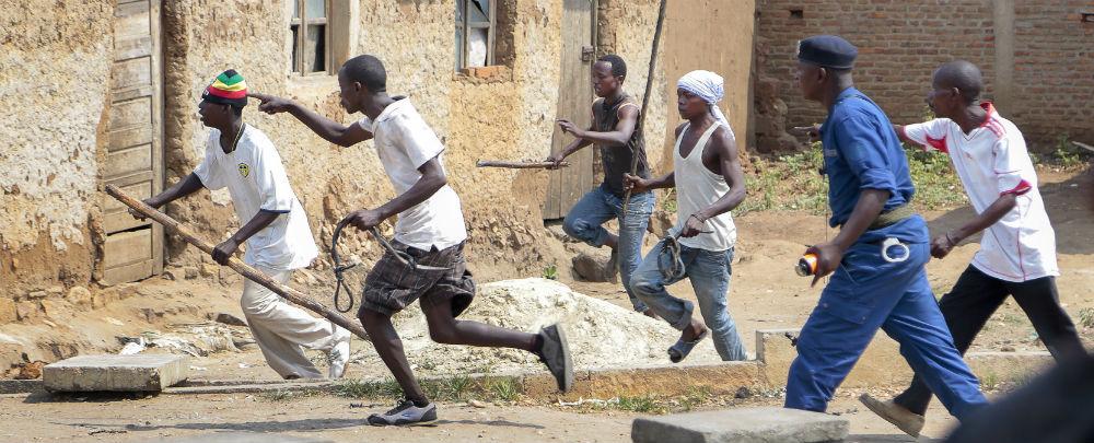 Des membres de la milice de jeunesse pro-gouvernementale Imbonerakure pourchassent des manifestants de l'opposition à Bujumbura le 25mai 2015, sous le regard d'un membre de la police (en bleu)
