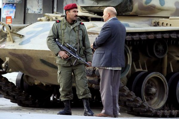 A Tunisian citizen talking to a member of the national guard